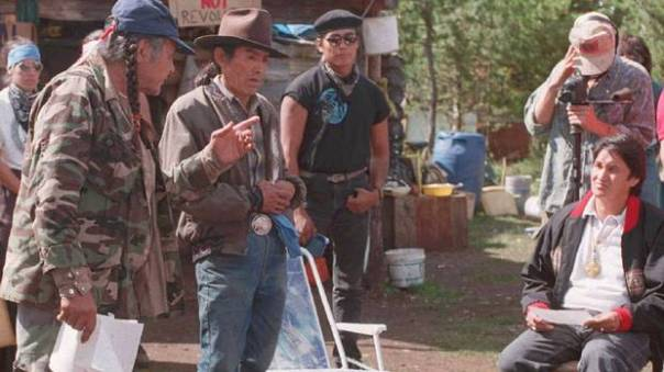 Ovide Mercredi, seated, then head of the Assembly of First Nations, meets with elders Wolverine and Percy Rosette at Ts'Peten, 1995.