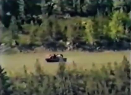 Still from RCMP Wescam surveillance footage showing the defender's truck driving down a dirt road at Gustafsen Lake, BC, 1995, moments before an explosive devise is detonated.