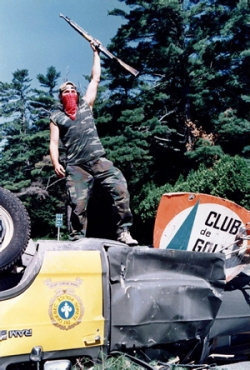 Warrior at Oka, 1990, standing on top of abandoned & over turned police car.