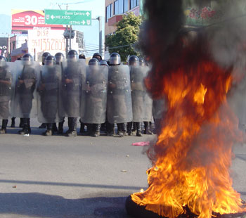 Oaxaca, riot police and burning tire barricade.