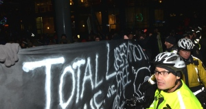 Cop screened by black bloc banner.