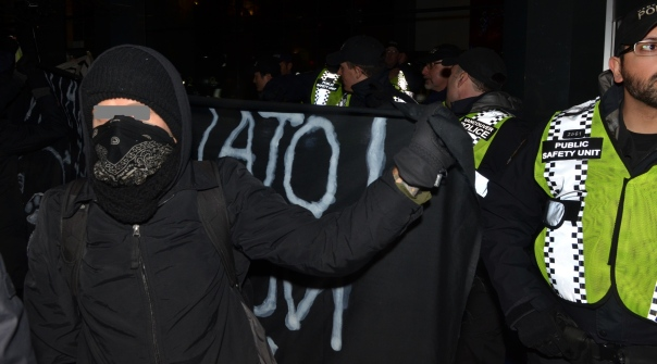 Masked militant holds up banner as screen during anti-Enbridge rally in Vancouver, Jan 14, 2013.