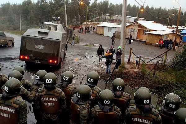 Chilean riot police raid a Mapuche village.