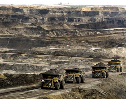 Massive trucks haul oil-laden sand in Alberta Tar Sands.