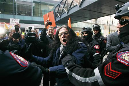 Dacajeweiah being arrested in Calgary, 2009, during at attempted citizen's arrest of former US president George W. Bush.