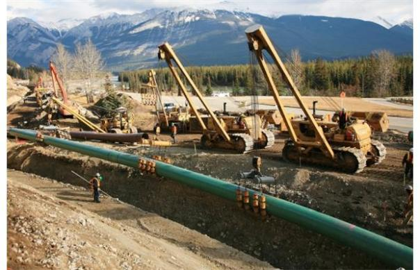 Kinder Morgan's Trans Mountain pipeline expansion: lowering pipes into trench.