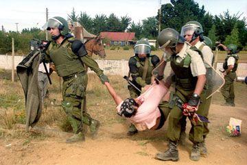 Chilean riot police arrest a Mapuche.