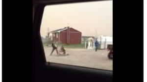 Frame from Youtube video showing SQ striking a prone Innu man.
