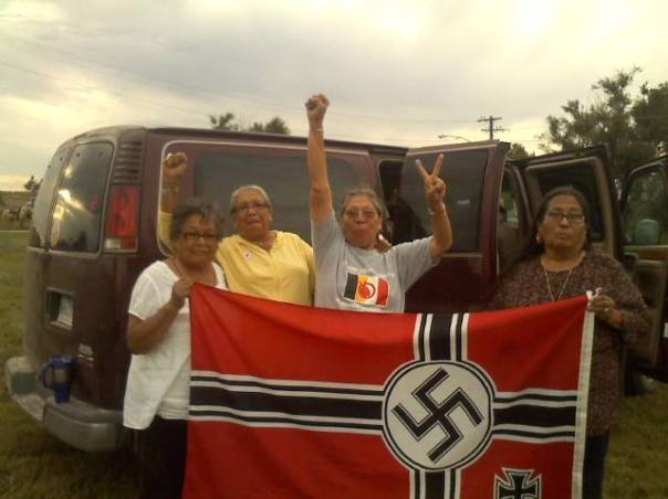 Lakota and Dakota elders with captured Nazi flag, later burned.