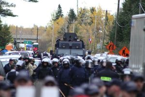 Colonial terrorism: RCMP Tactical Armoured Vehicle lurks in the background behind riot cops, Oct 17, 2013.