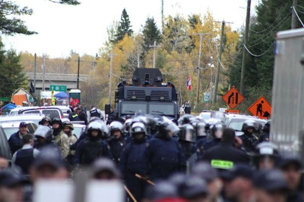 RCMP Tactical Armoured Vehicle lurks in the background behind riot cops, Oct 17, 2013.