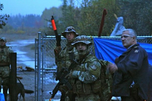 RCMP ERT members during early morning raid on camp, Oct 17, 2013.  The shot gun with the orange stock fires less lethal rounds, such as bean bags, rubber pellets, or rubber bullets.