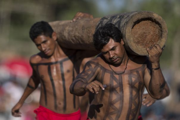 Xerente Indians demonstrate their traditional tree trunk race during the Indigenous Games in Cuiaba, Brazil, Friday, Nov. 15, 2013.