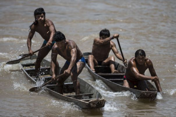 Indians from the Indian tribes, Enawene Nawe, left, and Kuikuro, right, compete in the canoeing competition at the Indigenous Games in Cuiaba, Brazil, Friday, Nov. 15, 2013.