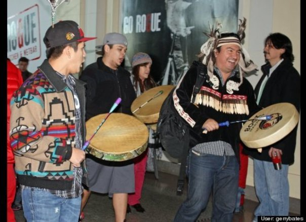Ian Campbell (on right) a Squamish chief, leading the singing as part of INM flash mob in Vancouver, 2012; Campbell also sang and danced for the 2010 Winter Olympics which was resisted by grassroots Natives.