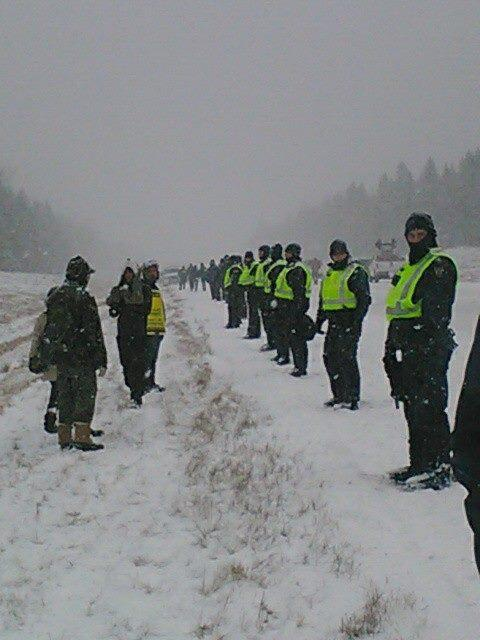 RCMP tactical troop members line Highway 11 to protect SWN vehicles, Dec 1, 2013.