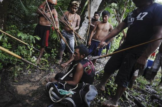Munduruku Indian warriors stand guard over an illegal gold miner who was detained by a group of warriors searching out illegal gold mines and miners in their territory near the Caburua river, a tributary of the Tapajos and Amazon rivers in western Para state January 20, 2014.