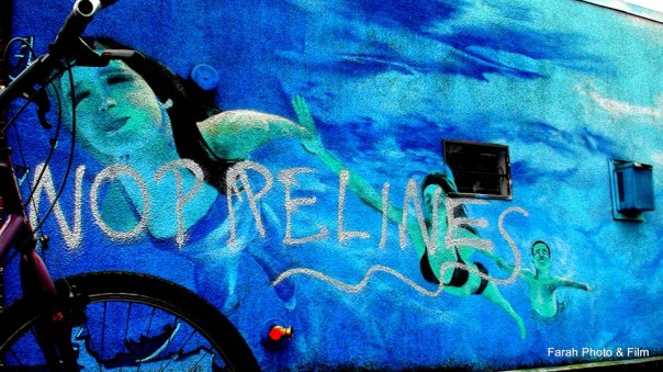 "Business mural with ""No Pipelines"" spray painted on it, Commercial Drive, Vancouver."