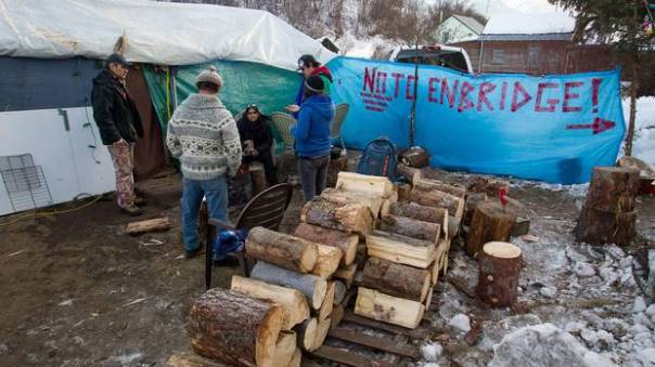 Members of the Gitxsan First Nation opposed to the $5.5-billion Enbridge oil pipeline from Alberta to the British Columbia port of Kitimat warm themselves around a fire at a camp outside the Gitxsan Treaty Office in Hazelton, B.C., on Thursday January 12, 2012.