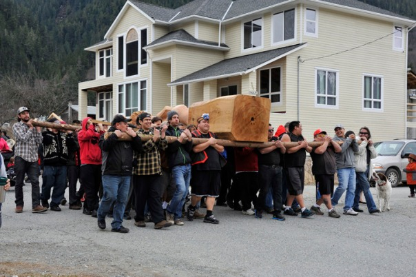 Nuxalk carry the Sputc totem pole through the village of Bella Coola.