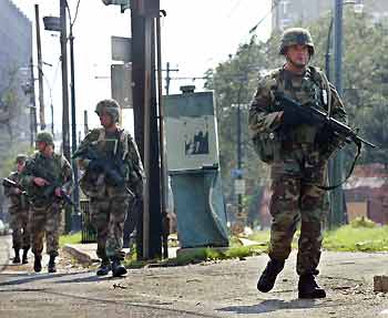 US National Guard soldiers patrol the streets of New Orleans in the aftermath of Hurricane Katrina, 2005.