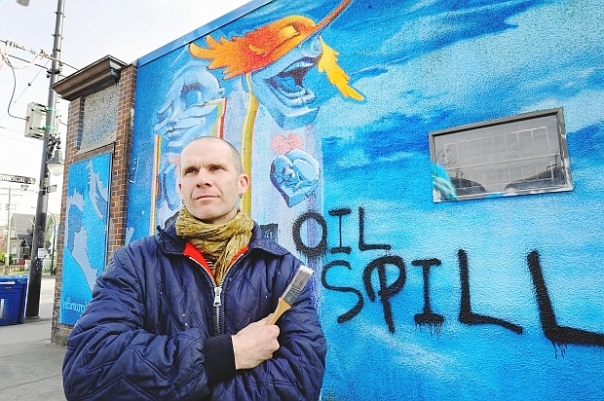 "Mural artist Milan Basic standing in front of his mural that has been spray-painted with ""Oil Spill."""
