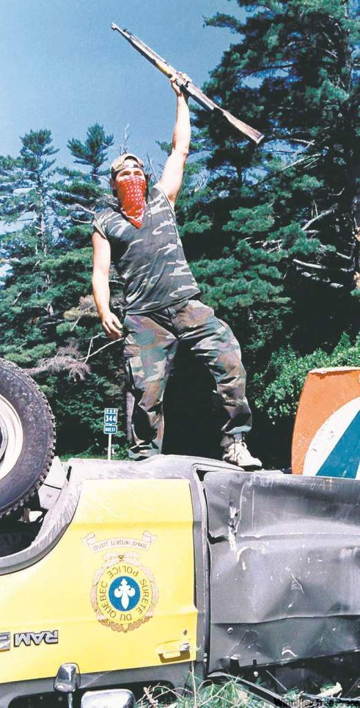 Warrior raises rifle from atop an overturned police cruiser at Oka roadblock in Quebec on July 1990. Photo by Tom Hanson / The Canadian Press.