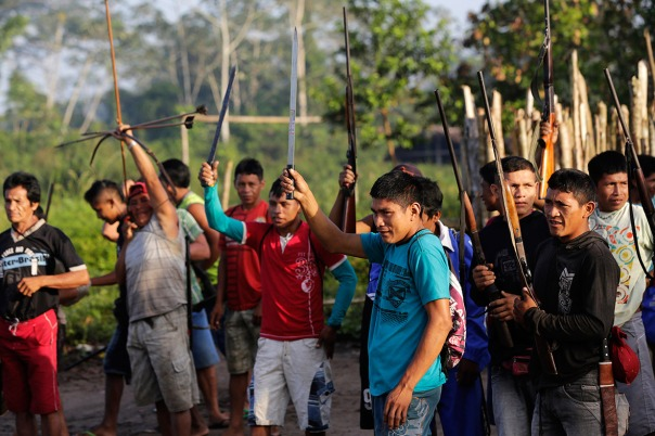 Ka'apor warriors raise their weapons as they leave the village of Waxiguy Renda to look for loggers in the Amazon.