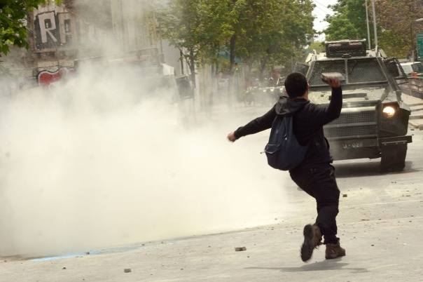 Militant throwing brick at armoured police vehicle during anti-Columbus Day protests in Santiago, Chile, 2014.