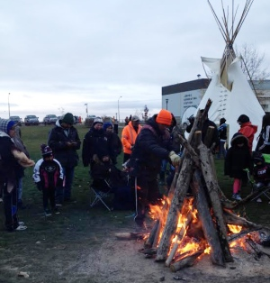 Members of Pimicikamak First Nation gather around fire during occupation of Manitoba Hydro Jenpeg station.