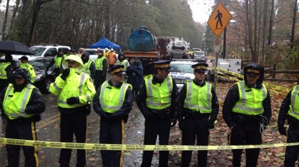 RCMP stand in guard of Kinder Morgan contractor's heavy equipment, Nov 21, 2014.