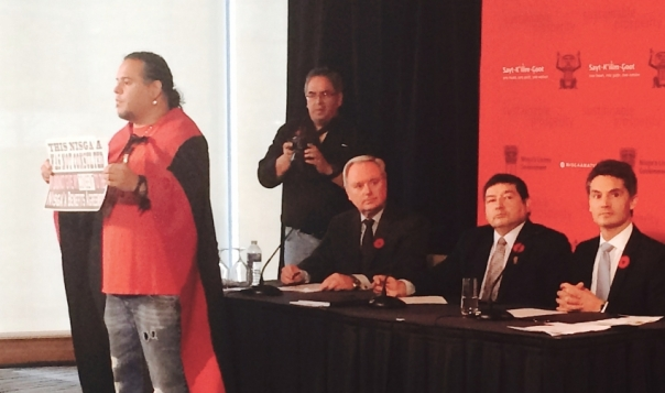 Photo of NorthWest LNG, Nisga'a' and PRGT presidents at signing ceremony with Grant Barton protesting by Sindhu Dharmarajah
