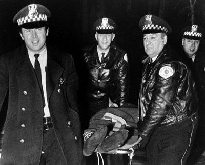 Chicago pigs smiling as they carry the body of Hampton, Dec 4, 1968.
