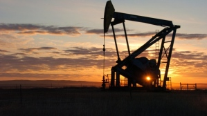 A Whiting Petroleum Co. pump jack pulls crude oil from the Bakken region of the Northern Plains near Bainville, Mont. U.S. shale oil is contributing to a worldwide glut that could drive the price of crude to $60. (Matthew Brown/Associated Press) .