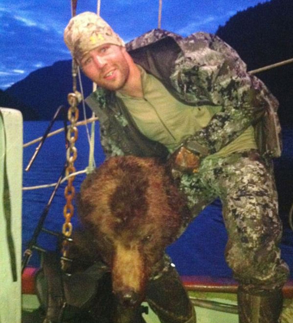 NHL defenceman Clayton Stoner posing with a beheaded grizzly in 2013.  Photo by Coastal Guardian Watchmen.