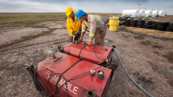 Two men work at the fuel storage site at the proposed Kiggavik uranium mine, near Baker Lake, Nunavut. (The Canadian Press).