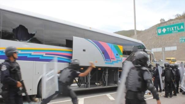 Riot police smash out the windows of a bus carrying normalista students, March 28, 2015.