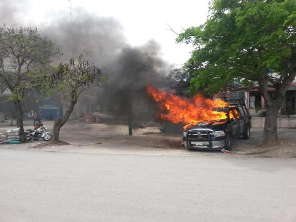 A police car burns after normalista students attack police station, March 28, 2015.