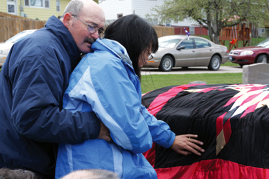 Jerry Capps, Rapid City, comforts his wife, Jaylene, as she grieves, touching the star quilt on the casket of her son, Christopher J. Capps, 22, during burial ceremonies on May 7, 2010. at Mountain View Cemetery, Rapid City. Photo by Randall Howell