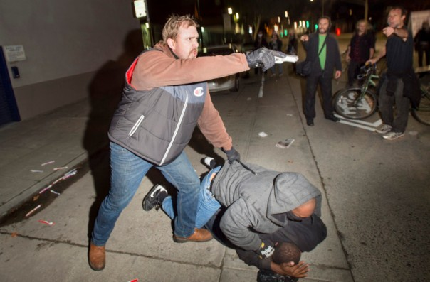 An undercover police officer, who had been marching with anti-police demonstrators, aims his gun at protesters after some in the crowd attacked him and his partner in Oakland, California December 10, 2014.