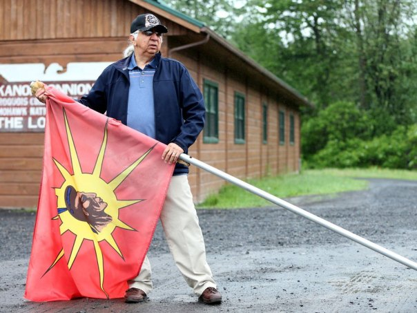 Kenneth Deer, poses with a flag outside a longhouse in Kahnawake, Quebec, June 2, 2015. Photo by Christinne Muschi for National Post.