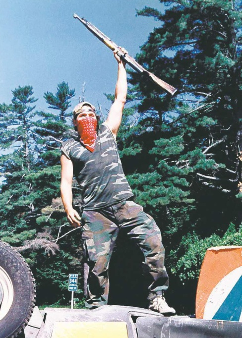 Mohawk warrior with SKS rifle stands atop overturned police car, July 11, 1990.