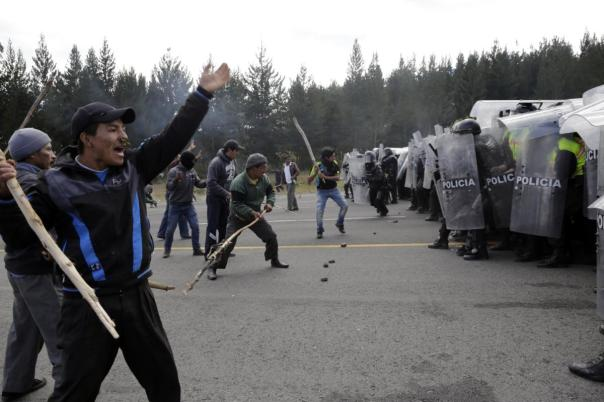 Indigenous protesters confront security forces during a general strike in El Chasqui, Ecuador, Thursday, Aug. 13, 2015. A strike by a broad coalition upset with President Rafael Correa virtually paralyzed the capital, provincial cities and stretches of the Panamerican highway. The protesters are indigenous activists, unionists, environmentalists and members of the traditional political opposition. (AP Photo/Dolores Ochoa)