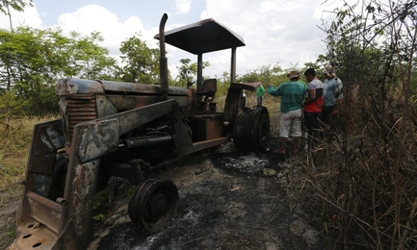 Ka'apor Indians stand next to a logging tractor that they discovered and set on fire inside the indigenous territory one month before. Photograph: Lunae Parracho/Greenpeace