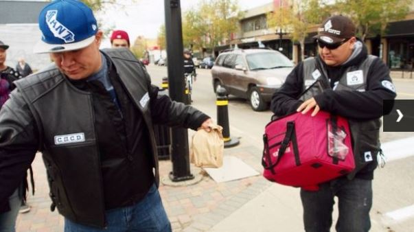 Leonard Saddleback grabs sack lunches from Chris Martell to hand out along 20th St W. in Saskatoon. (Josh Lynn/CBC)
