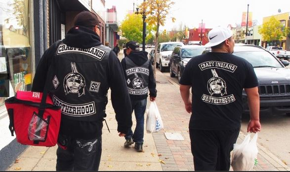 Crazy Indians Brotherhood members carry bags of sack lunches down 20th St W. in Saskatoon. (Josh Lynn/CBC)