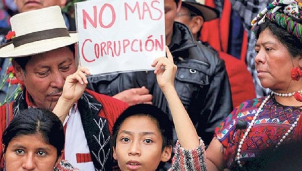 "Indigenous protesters hold a sign saying ""no more corruption"" in Guatemala City, August 2015. Photo: Reuters"