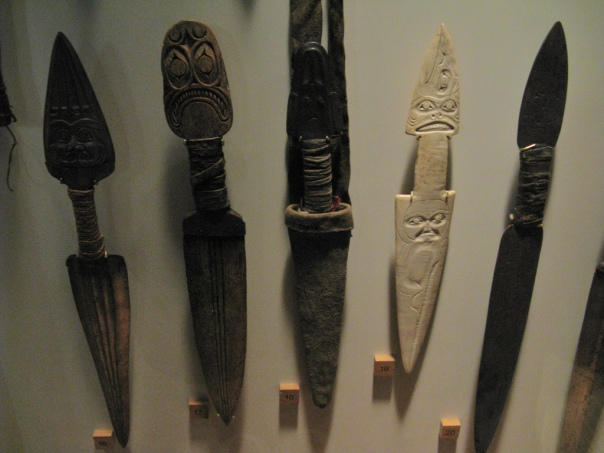 Field Museum of Natural History, located in Chicago, Illinois, The outside two knives are of Tlingit design. The one on the left is made of iron and has a face representing a dogfish shark. The far right dagger looks to also be made of metal but has just a faint design. The second dagger from the left was made of bone by a Kwakiutl person. It too has a dogfish shark design, although the eyes on this one are a bit more convincing. The middle dagger and the one to the right of it are both made by Haida people and may be made of stone and bone respectively. The middle dagger belonged to Chief Moses, who lived in eastern Washington up to the end of the 19th century when he passed away. The whitish dagger has carved on it two ravens, a man, and a dogfish. Flickr