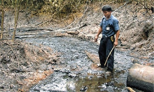 Achuar leader Carlos Sandi observes the damage left behind by extractionist oil companies.  Photo: Reuters