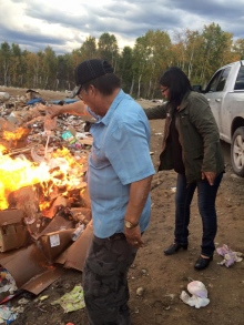 Councillors from the North Caribou Lake First Nation burn confiscated booze over a fire at the local garbage dump on Monday, Sept. 21, 2015. (Facebook)